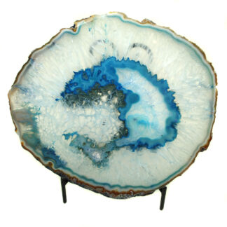 An agate slice dyed blue with an intricate center and well defined banding along the edges against a white background