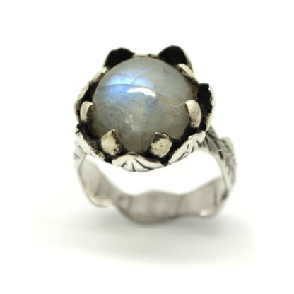 A round rainbow moonstone cabochon set in a floral themed sterling silver ring against a white background