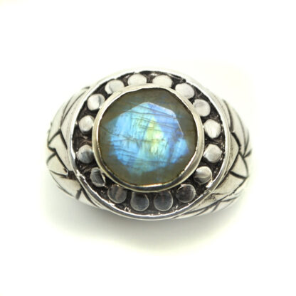 A faceted oval rainbow moonstone cabochon set in an intricate sterling silver ring against a white background