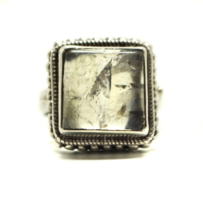 A square rainbow moonstone cabochon set in a sterling silver ring against a white background