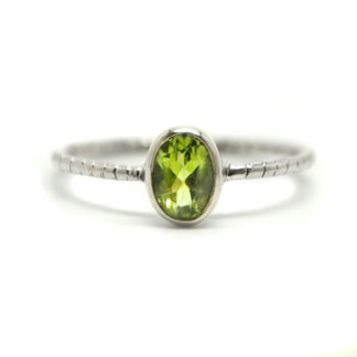 An oval faceted peridot gemstone set in a dainty sterling silver ring against a white background