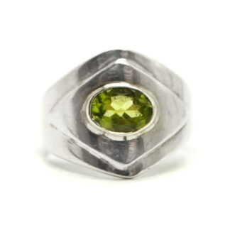 A peridot gemstone faceted into an oval and set into a diamond shaped sterling silver ring against a white background