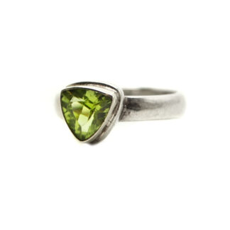 A peridot gemstone faceted into a trilliant and set into a simple sterling silver ring with a thin band against a white background