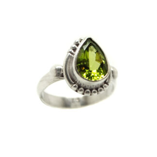 A peridot gemstone faceted into an teardrop and set into a decorative sterling silver ring with a thin band against a white background