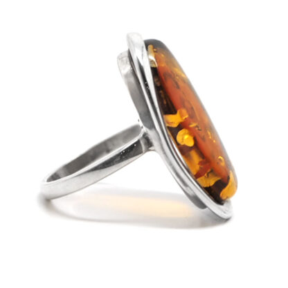 A sterling silver ring with a thin band featuring an oval baltic amber cabochon against a white background