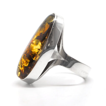 A sterling silver ring with a thick band featuring an oval baltic amber cabochon against a white background