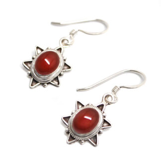 A pair of decorative sterling silver earrings set with deep orange carnelian agate cabochons against a white background