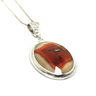 A faceted carnelian oval cabochon set into a sterling silver pendant with an intricate bail against a white background