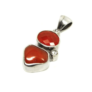 A sterling silver pendant featuring a faceted red carnelian cabochon, a polished red carnelian cabochon, and a small faceted white topaz gemstone against a white background
