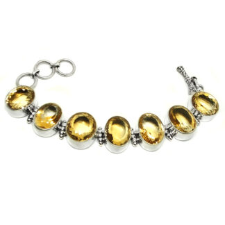 A chunky, oval-faceted citrine sterling silver bracelet against a white background