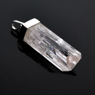 A transparent pale pink danburite crystal pendant in sterling silver against a black background
