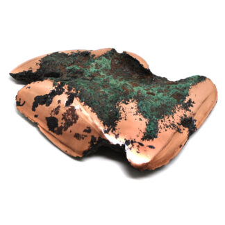 A piece of float copper with green oxidation against a white background
