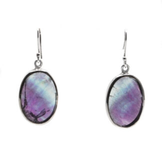 A pair of sterling silver oval earrings with teal and purple fluorite cabochons against a white background