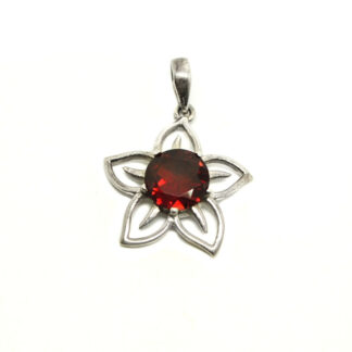 A faceted red garnet gemstone set into a sterling silver flower shaped pendant against a white background