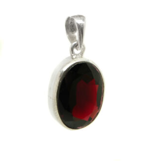 A faceted red garnet gemstone set into an oval sterling silver pendant against a white background