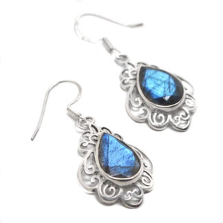 A pair of ornate sterling silver earrings with faceted teadrop labradorite cabochons against a white background