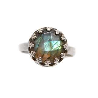 A round faceted labradorite cabochon set into a sterling silver ring featuring a crown style bezel against a white background