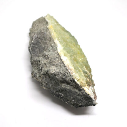 A large cluster of well-defined light green prehnite crystals in a grey matrix against a white background