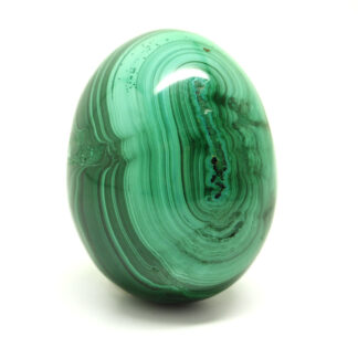 A piece of malachite carved and polished into an egg against a white background
