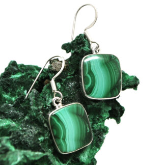 A pair of sterling silver malachite dangle earrings propped up against a rough malachite specimen against a white background