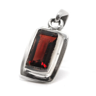 A sterling silver pendant with a faceted rectangle garnet gemstone against a white background
