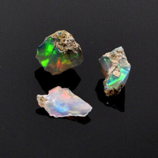 A set of 3 colorful ethiopian opals against a black background