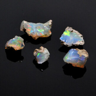 A set of 5 colorful ethiopian opals against a black background