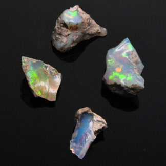 A set of 4 colorful ethiopian opals against a black background
