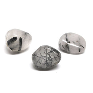 A set of 3 tumbled tourmalinated quartz stones against a white background