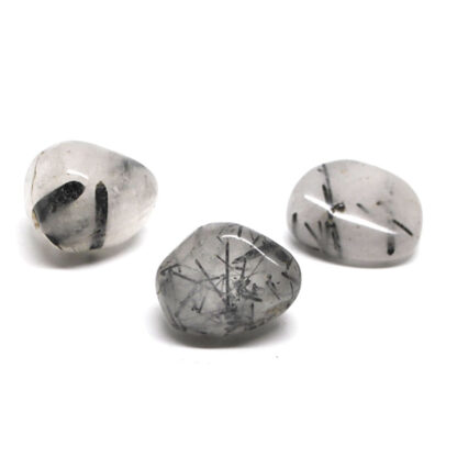 A set of 3 tumbled tourmalinated quartz stones against a white background