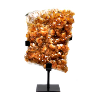 A citrine cluster on a wrought iron stand against a white background