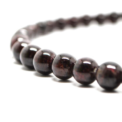 A beaded garnet necklace against a white background