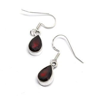 A pair of faceted red garnet gemstones set into simple sterling silver earrings against a white background