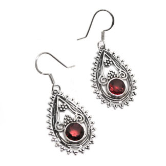 A pair of ornate sterling silver earrings with faceted garnet gemstones against a white background
