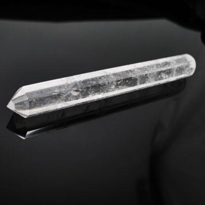 A clear quartz wand against a black background