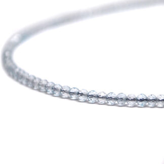 A blue topaz microbead necklace against a white background