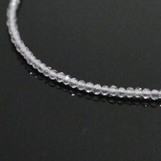 A white topaz microbead necklace against a black background