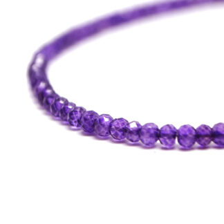 A deep purple amethyst microbead bracelet with a sterling silver lobster claw clasp against a black background