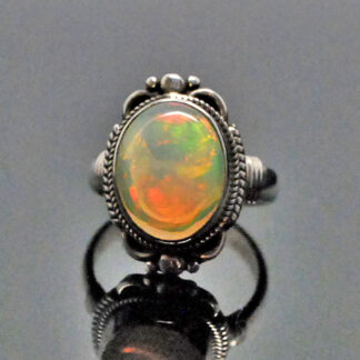 An ornate sterling silver ring featuring an oval Ethiopian opal with rainbow play of color against a grey background