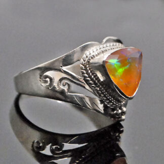 An ornate sterling silver ring featuring a trilliant Ethiopian opal with rainbow play of color against a grey background