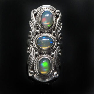 An ornate sterling silver ring featuring 3 oval ethiopian opals with rainbow play of color against a black background