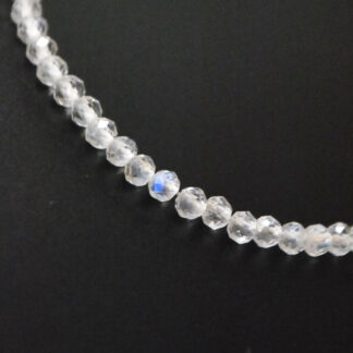 A rainbow moonstone microbead bracelet with a sterling silver lobster claw clasp against a black background