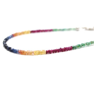 A ruby, emerald, and sapphire microbead bracelet with a sterling silver lobster claw clasp against a white background