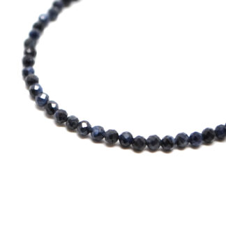 A dark blue sapphire microbead bracelet with a sterling silver lobster claw clasp against a white background
