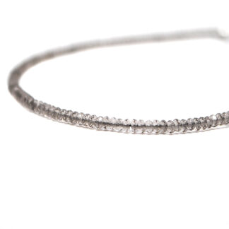 A smokey quartz microbead bracelet against a white background