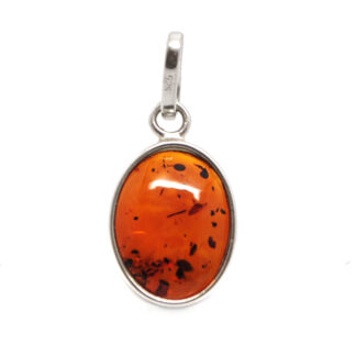 A polished piece of amber fastened with a sterling silver bail against a white background
