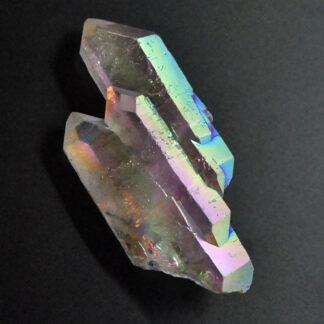 A platinum vapor treated iridescent quartz crystal against a black background