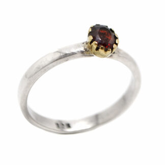 A sterling silver ring with a faceted deep red garnet gemstone set into a brass bezel against a white background