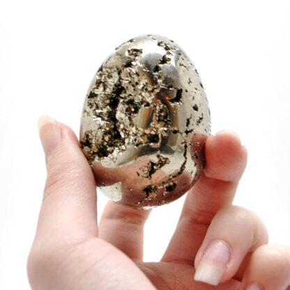 A hand holding a carved pyrite egg with exposed crystals against a white background