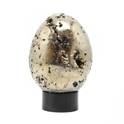 A carved pyrite egg with exposed crystals on a black acrylic ring stand against a white background